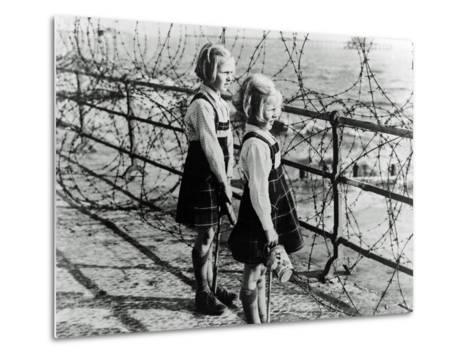 Two Girls on the South Coast of England Look Out Toward the Beach Through a Barbed Wire Fence--Metal Print