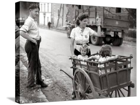 A French Couple with Two Young Girls in a Carriage Is Watching a Convoy of GMC Passing--Stretched Canvas Print