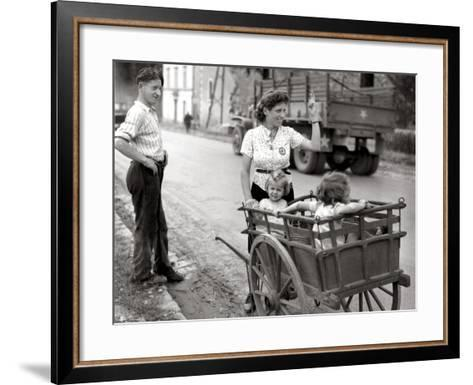 A French Couple with Two Young Girls in a Carriage Is Watching a Convoy of GMC Passing--Framed Art Print