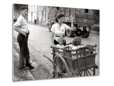 A French Couple with Two Young Girls in a Carriage Is Watching a Convoy of GMC Passing--Metal Print