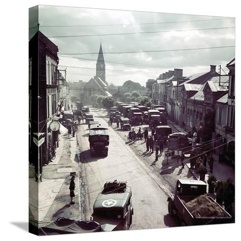 United States Army Trucks, Jeeps and Other Vehicles Entering a Town in Normandy, France, June 1944--Stretched Canvas Print