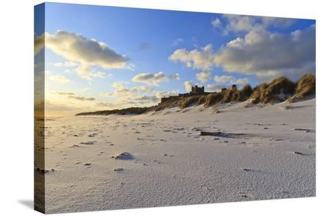Fresh Spring Snow at Dawn Highlight Ripples and Marks in the Sand Beneath Bamburgh Castle-Eleanor-Stretched Canvas Print