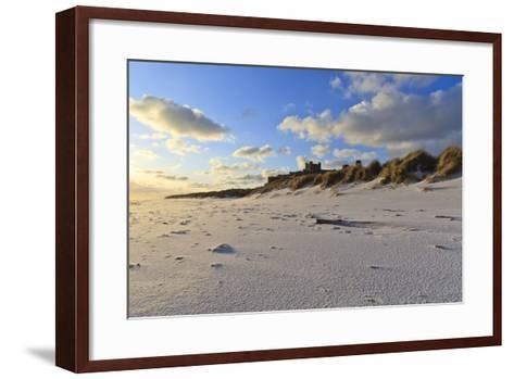 Fresh Spring Snow at Dawn Highlight Ripples and Marks in the Sand Beneath Bamburgh Castle-Eleanor-Framed Art Print