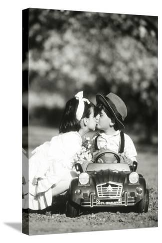 Children Kiss in Toy Car--Stretched Canvas Print
