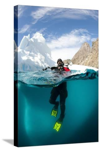 Diver in Front of an Iceberg, Astrolabe Island, Antarctic Peninsula, Antarctica--Stretched Canvas Print