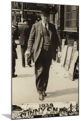 Man in a Bowler Hat Walking Along a Street, 1938--Mounted Photographic Print