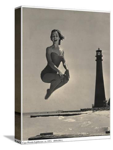 Woman Jumping in Front of Cape Florida Lighthouse, C.1975--Stretched Canvas Print