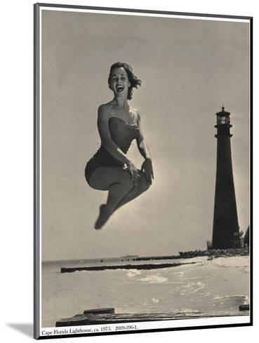 Woman Jumping in Front of Cape Florida Lighthouse, C.1975--Mounted Photographic Print