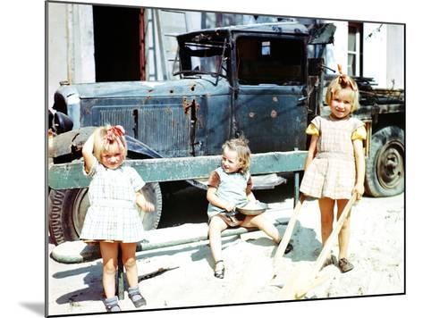 Three Girls Playing in the Sand Next to a War-Damaged Vehicle, Cherbourg, France, July 1944--Mounted Photographic Print