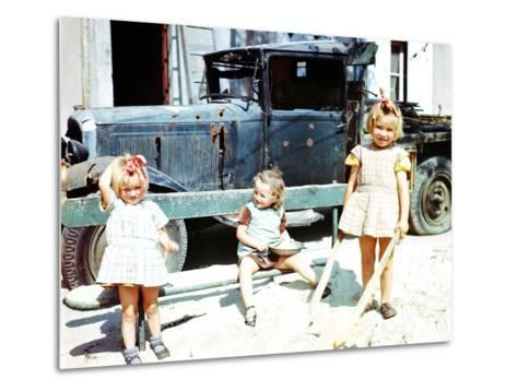 Three Girls Playing in the Sand Next to a War-Damaged Vehicle, Cherbourg, France, July 1944--Metal Print