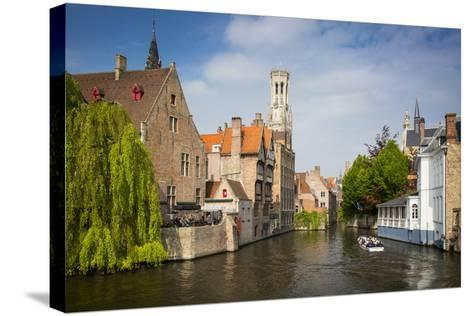 Tourist on Boat Ride Through the Canals of Bruges, Belgium-Brian Jannsen-Stretched Canvas Print