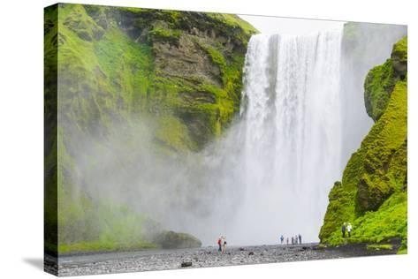Iceland. South. Skogafoss. Hikers are Skogafoss Waterfall-Inger Hogstrom-Stretched Canvas Print