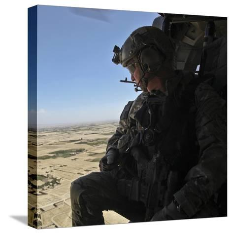 A U.S. Army Special Forces Soldier Looks Out from a Uh-60 Black Hawk--Stretched Canvas Print