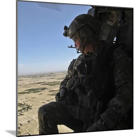 A U.S. Army Special Forces Soldier Looks Out from a Uh-60 Black Hawk--Mounted Photographic Print