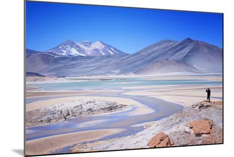 Man Standing on Rocks Looking over Miscanti Laguna, Turquoise Mineral Lake, San Pedro De Atacama-Kimberly Walker-Mounted Photographic Print