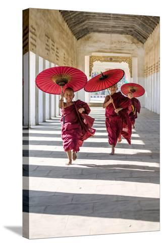 Myanmar, Mandalay Division, Bagan. Three Novice Monks Running with Red Umbrellas in a Walkway (Mr)-Matteo Colombo-Stretched Canvas Print