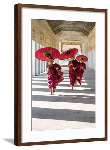 Myanmar, Mandalay Division, Bagan. Three Novice Monks Running with Red Umbrellas in a Walkway (Mr)-Matteo Colombo-Framed Art Print