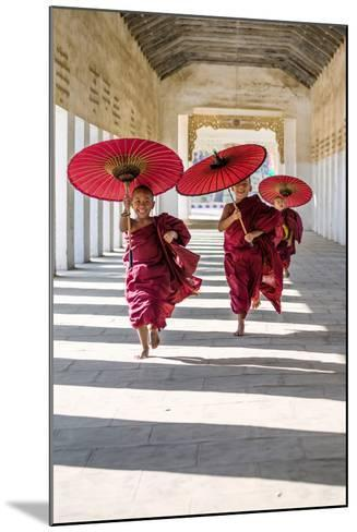 Myanmar, Mandalay Division, Bagan. Three Novice Monks Running with Red Umbrellas in a Walkway (Mr)-Matteo Colombo-Mounted Photographic Print