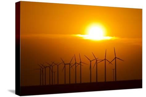 The Sun Sets Behind a Row of Spinning Windmills or Wind Turbines-Mike Theiss-Stretched Canvas Print