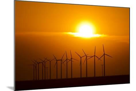 The Sun Sets Behind a Row of Spinning Windmills or Wind Turbines-Mike Theiss-Mounted Photographic Print