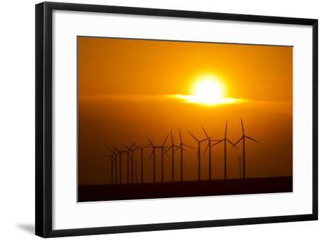 The Sun Sets Behind a Row of Spinning Windmills or Wind Turbines-Mike Theiss-Framed Art Print