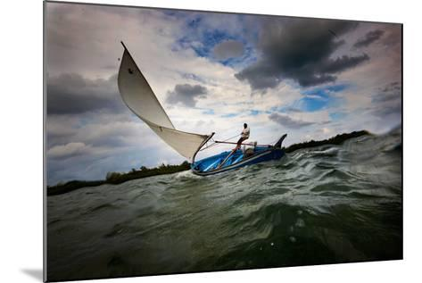 A Man Sails a Boat Off the Cayman Islands in the Caribbean-Chris Bickford-Mounted Photographic Print