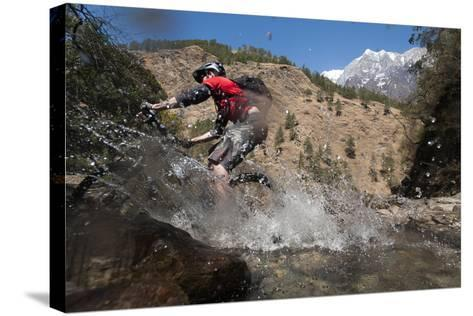 A Mountain Biker Blasts Through a Stream in the Mountains of Nepal-Alex Treadway-Stretched Canvas Print