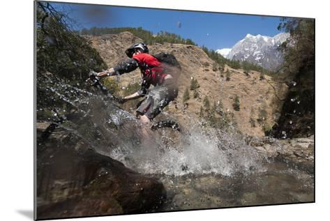 A Mountain Biker Blasts Through a Stream in the Mountains of Nepal-Alex Treadway-Mounted Photographic Print