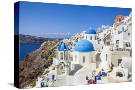 Greek Church with Three Blue Domes in the Village of Oia-Neale Clark-Stretched Canvas Print