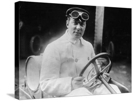 A Man at the Wheel of His Car Dressed in a Driving Coat and Goggles--Stretched Canvas Print