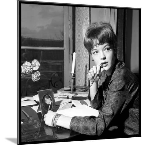 Romy Schneider, Thougthful, Trying to Write a Letter in Front of Alain Delon's Picture-Marcel Begoin-Mounted Photographic Print