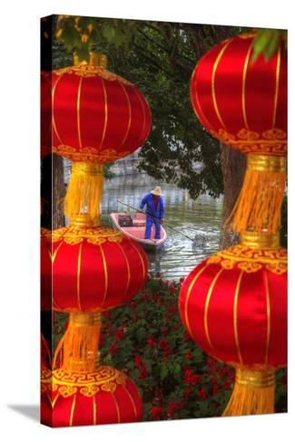 Worker in Boat Cleaning Green Lake, Kunming China-Darrell Gulin-Stretched Canvas Print