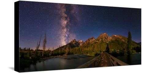 The Night Sky over a Bridge in Grand Teton National Park-Babak Tafreshi-Stretched Canvas Print
