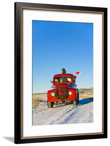 Santa Driving a Vintage Red Ford Pick-Up Truck Down a Snowcovered Rural Road-Design Pics Inc-Framed Art Print