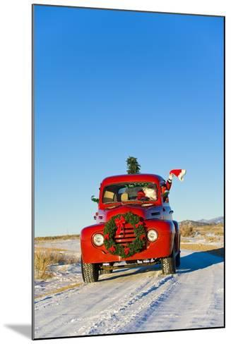 Santa Driving a Vintage Red Ford Pick-Up Truck Down a Snowcovered Rural Road-Design Pics Inc-Mounted Photographic Print