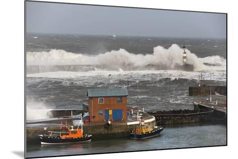 Seaham, Teesside, England; Waves Crashing into a Lighthouse and Boats Along a Pier-Design Pics Inc-Mounted Photographic Print