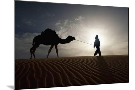 Silhouette of Berber Leading Camel across Sand Dunes at Dusk in the Erg Chebbi-Design Pics Inc-Mounted Photographic Print