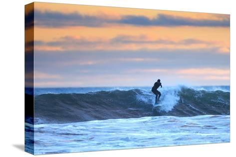 A Surfer Rides a Winter Wave Off the Coast of Maine at Sunset-Robbie George-Stretched Canvas Print