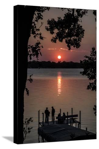 Residents Watch a Late Summer Sunset from their Dock on West Okoboji Lake-Kent Kobersteen-Stretched Canvas Print