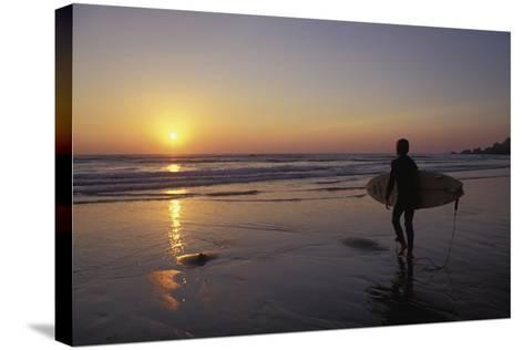 Silhouetted Surfer on Sandy Beach at Sunset-Design Pics Inc-Stretched Canvas Print