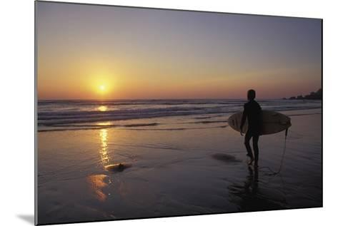 Silhouetted Surfer on Sandy Beach at Sunset-Design Pics Inc-Mounted Photographic Print