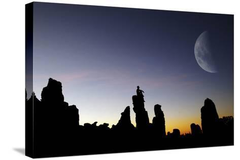 Composite Image of a Man Sitting on Top of a Small Pillar at Sunset, Looking at a Moon-Keith Ladzinski-Stretched Canvas Print