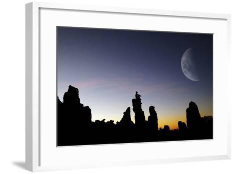 Composite Image of a Man Sitting on Top of a Small Pillar at Sunset, Looking at a Moon-Keith Ladzinski-Framed Art Print