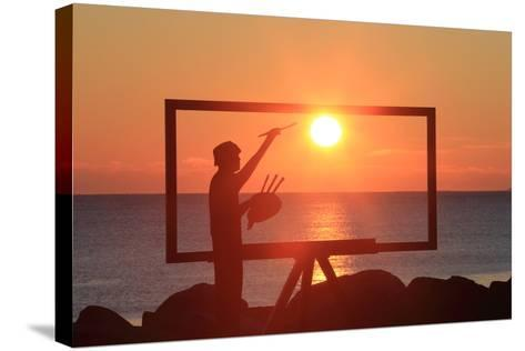 A Sculpture of an Artist Painting in New Castle, New Hampshire Frames the Sunrise-Robbie George-Stretched Canvas Print