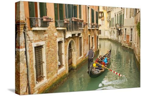 Tourists Ride in a Gondola in a Canal Winding Through Venice-Mike Theiss-Stretched Canvas Print