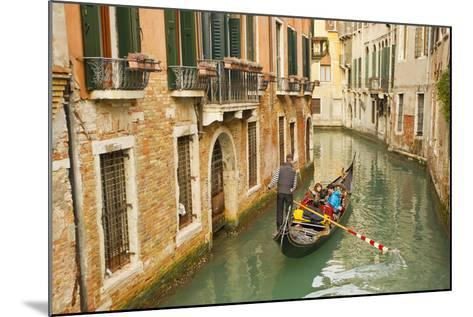 Tourists Ride in a Gondola in a Canal Winding Through Venice-Mike Theiss-Mounted Photographic Print