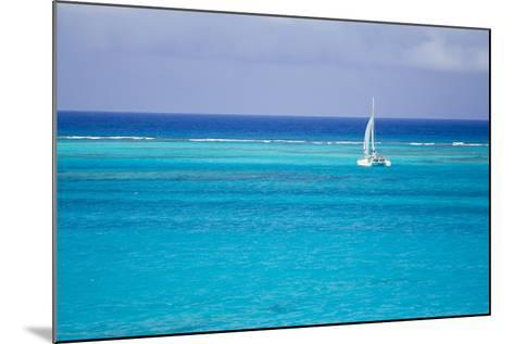 A Lone Sailboat in Turquoise Caribbean Waters Just Offshore-Mike Theiss-Mounted Photographic Print