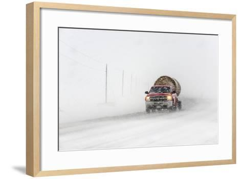 A Pickup Truck Pulling Hay Bales Drives Through Blizzard Conditions-Jim Reed-Framed Art Print