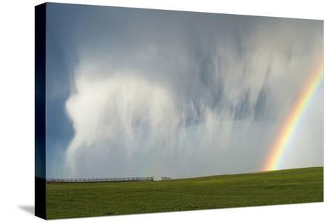 A Thunderstorm Produces a Curtain of Falling Hailstones Next to a Rainbow-Jim Reed-Stretched Canvas Print
