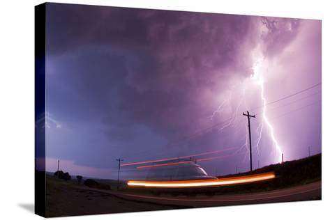 A Large Lightning Bolt Strikes Behind a Storm Chaser's Moving Van-Mike Theiss-Stretched Canvas Print
